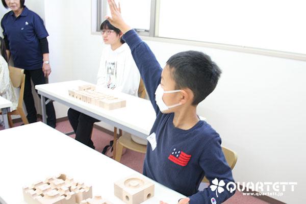 小学生の男の子が元気よく手を挙げている